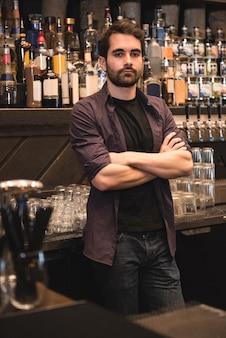 Barman confiant debout au comptoir du bar