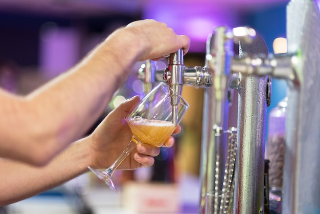 Barman dans le pub versant une bière blonde dans un verre