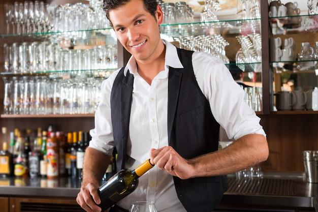 Barman debout derrière un bar avec du vin