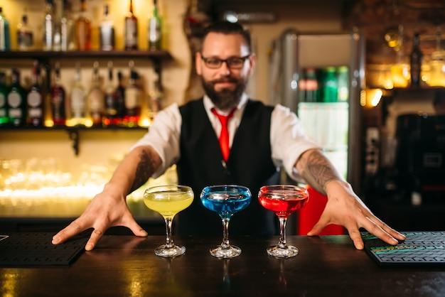 Le barman derrière le comptoir du bar montre des cocktails d'alcool