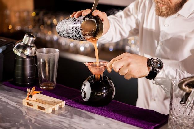 Le barman du barman verse un verre. boisson alcoolisée
