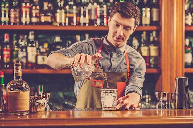 Un barman expert prépare un cocktail en boîte de nuit.