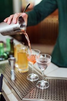Barman faisant un cocktail au bar: verser un verre d'un shaker dans un verre