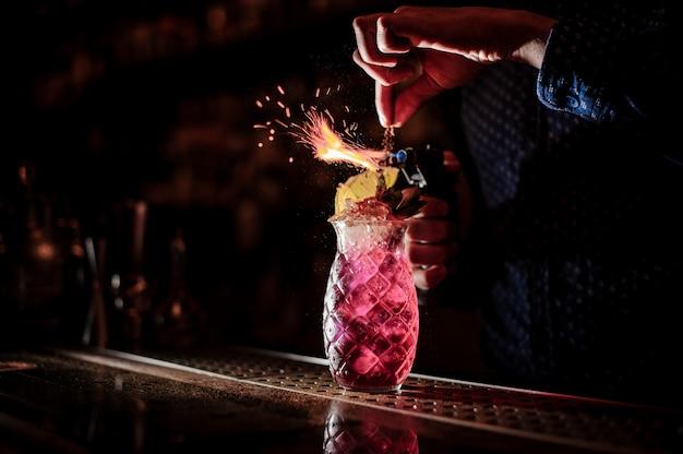 Barman faisant un cocktail d'été mojito aux fraises sucré et frais avec une note de fumée sur le fond sombre