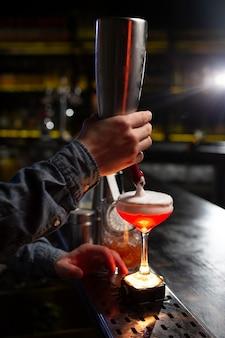 Barman faisant un cocktail avec un shaker