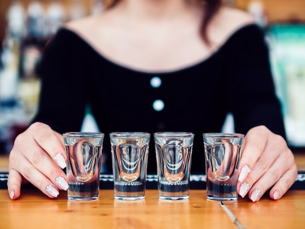 Barman féminin avec une rangée de verres à liqueur