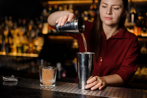 Barman fille faisant un cocktail au comptoir du bar