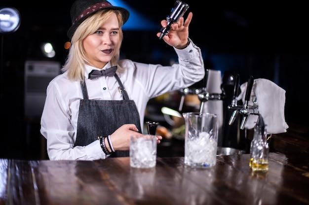 Barman fille mélange un cocktail dans la brasserie