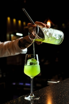 Barman mâle préparant un cocktail, versant une boisson verte d'un verre à mélange à travers une passoire dans un verre à vin avec un glaçon