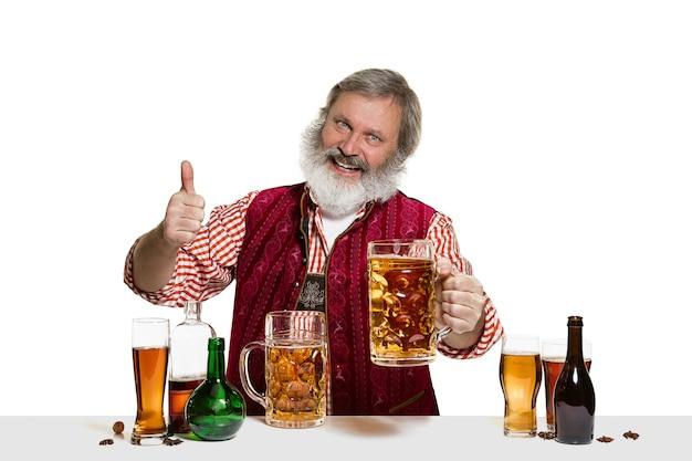 Le barman masculin expert senior avec de la bière au studio isolé sur un mur blanc