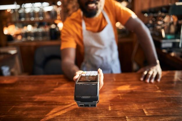 Barman masculin tenant le terminal pour le paiement sans contact