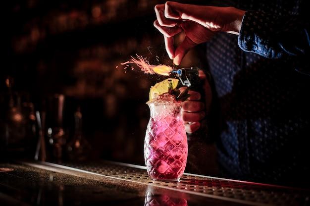 Barman part faire un cocktail d'été mojito fraise douce et fraîche avec une note de fumée sur le fond sombre