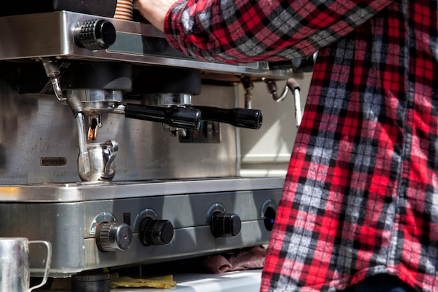 Le barman prépare le café, le cappuccino, le cacao et les boissons au bar. travail de barman.