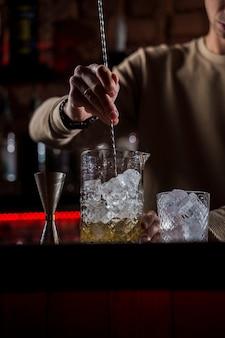 Le barman prépare un cocktail d'alcool au comptoir du bar. barman faisant un cocktail de jus de jungle au bar