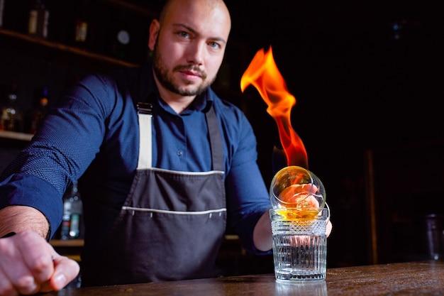 Le barman prépare un cocktail alcoolisé chaud et enflamme le verre