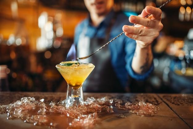 Le barman prépare un cocktail alcoolisé avec de la glace