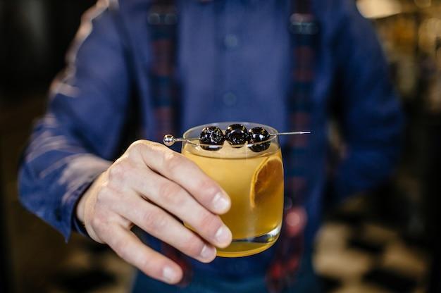 Le barman prépare un cocktail au bar.
