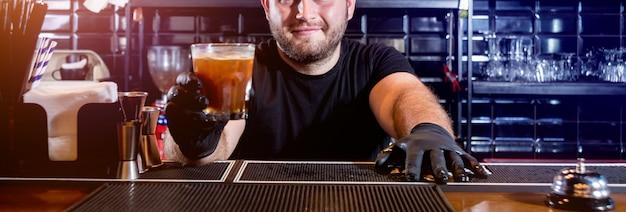 Le barman prépare un cocktail au comptoir du bar. cocktails frais. barman au travail. restaurant. la vie nocturne.