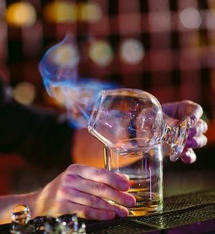 Le barman prépare un cocktail chaud.