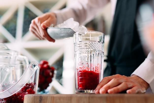 Le barman prépare un cocktail de fruits rouges sur la terrasse du restaurant.