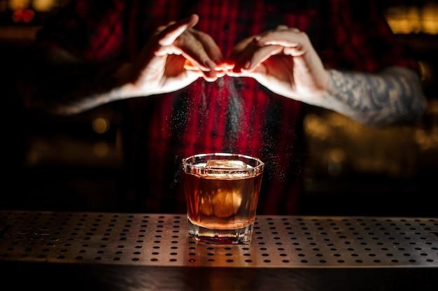 Barman professionnel en chemise rouge ajoutant du jus de zeste d'orange à un cocktail gin fizz dans le verre sur le comptoir du bar