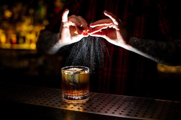 Barman professionnel en chemise rouge ajoutant du jus de zeste d'orange à un cocktail rusty nail dans le verre sur le comptoir du bar