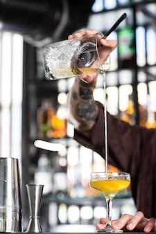 Un barman professionnel mélange un cocktail froid avec une cuillère plusieurs bouteilles de boissons alcoolisées