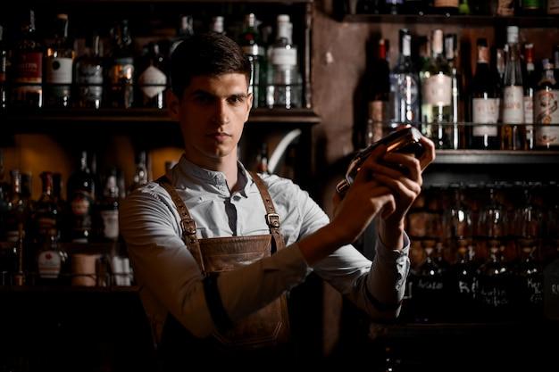 Barman professionnel tenant dans les mains un shaker en acier