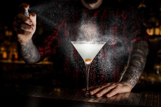 Barman pulvérisant amer sur le verre