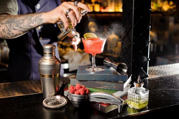 Barman pulvérisant de la tourbe amère sur un verre avec un cocktail d'été sucré rouge disposé sur des livres