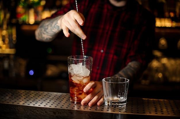 Barman remuant un cocktail de la légion étrangère avec la cuillère dans la tasse à mesurer sur le comptoir du bar
