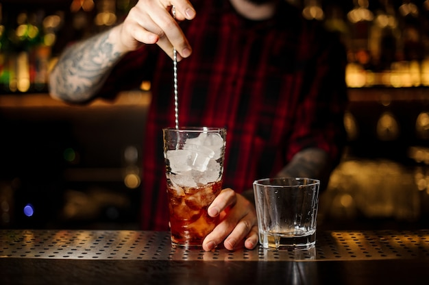 Barman remuant un cocktail de la légion étrangère avec la cuillère dans la tasse à mesurer en verre sur le comptoir du bar