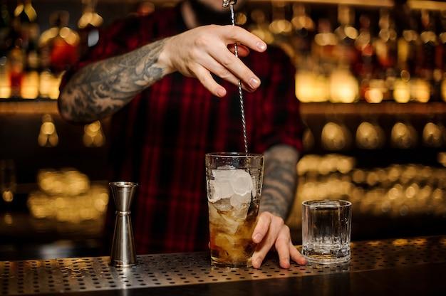 Barman remuant un cocktail rusty nail avec la cuillère dans la tasse à mesurer en verre sur le comptoir du bar