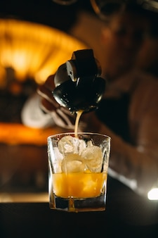 Le barman serre le jus d'agrumes dans un cocktail