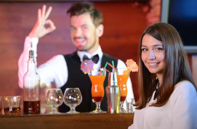 Barman servant un cocktail à une femme séduisante.