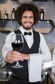 Barman servant un verre de vin rouge dans le comptoir du bar