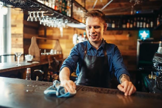 Barman en tablier nettoie le comptoir du bar après la fête