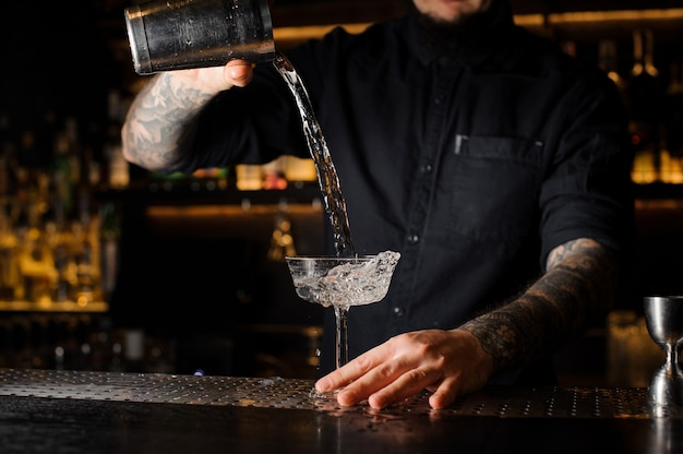 Barman tatoué versant une boisson alcoolisée du shaker en acier au verre à cocktail vide sur le comptoir du bar