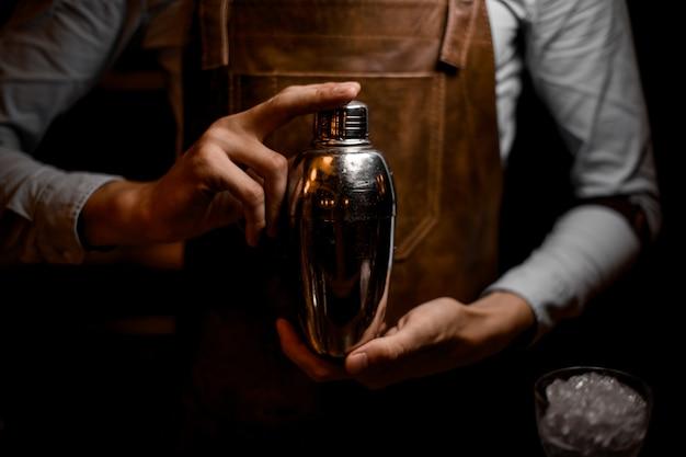 Barman tenant dans les mains un shaker en acier