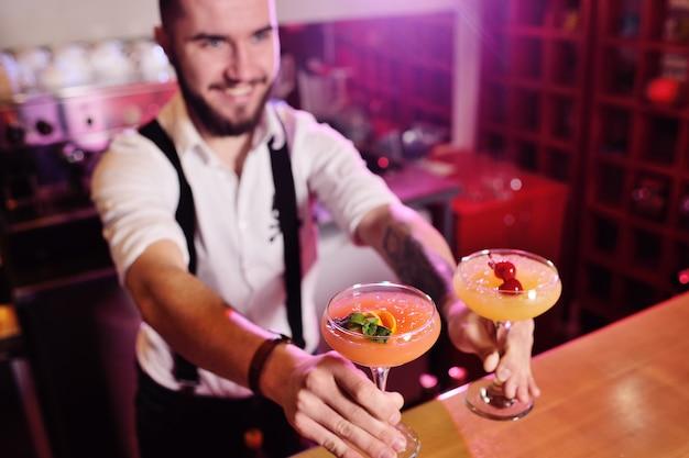 Le barman tenant deux verres avec un cocktail orange alcoolique sourit