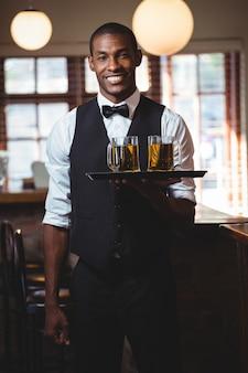 Barman tenant un plateau de service avec des verres de bière