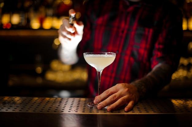 Barman vaporisant le cocktail courpse reviver depuis le vaporisateur spécial sur le comptoir du bar
