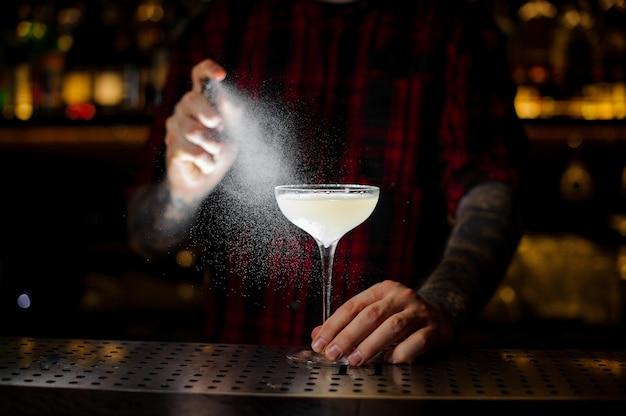 Barman vaporisant sur le cocktail courpse reviver du vaporisateur spécial dans l'obscurité sur le comptoir du bar