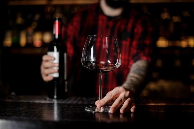 Barman avec un verre de burgunya vide et une bouteille de vin rouge