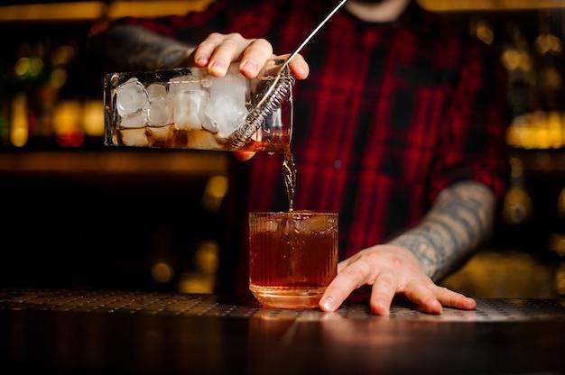 Barman versant un cocktail à l'ancienne de la tasse à mesurer avec passoire à un verre sur le comptoir du bar