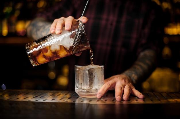 Barman versant un cocktail à l'ancienne de la tasse à mesurer à un verre sur le comptoir du bar