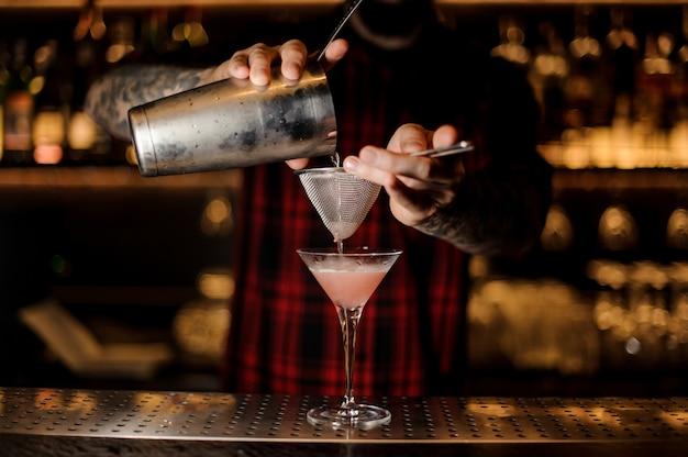 Barman versant un cocktail cosmopolitan dans un verre