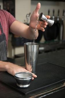 Barman versant un cocktail dans un shaker au comptoir du bar