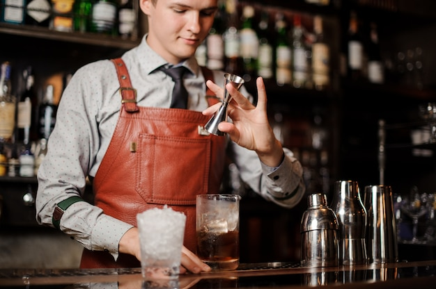 Barman versant un cocktail dans un verre