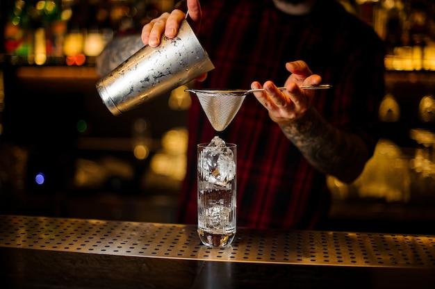 Barman versant un cocktail hurricane punch du shaker en acier sur le comptoir du bar
